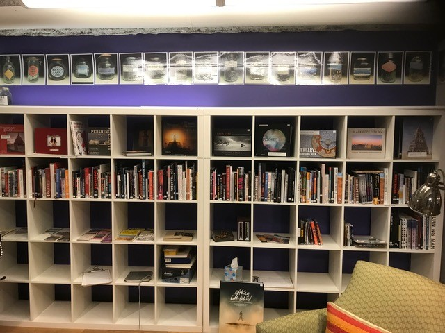 Shelves, that look like cubbies, with books.