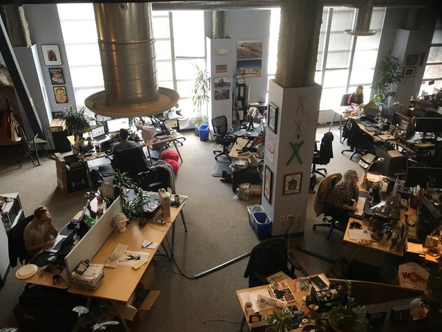 View of office space, lots of objects on desks and art on the walls and pillars.
