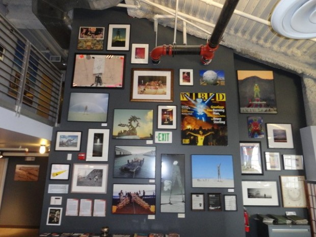 A wall of images from the 1990s, depicting history of Burning Man. Includes magazine covers and photographs.