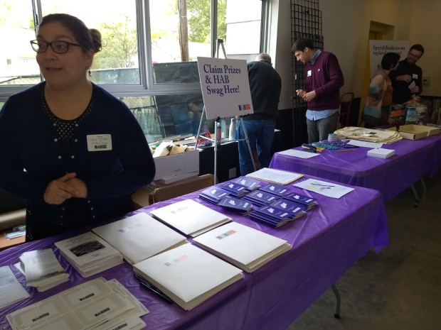 "Person with hair in bun with glasses standing behind table with purple table cloth with name tags, folders, booklets, and next to sign that says ""Claim Prizes & HAB Swag Here!"" Adjacent table with purple table cloth and 4 people standing behind it on right."