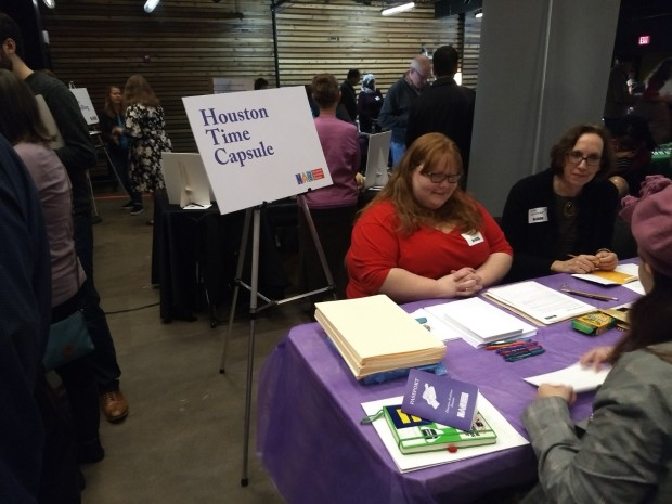 "Two people sitting behind table with purple table cloth with standing sign that says ""Houston Time Capsule"" standing to the left, person in front of table sitting and engaging."