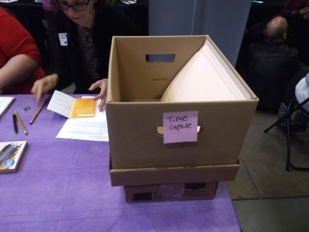 "Close up of brown box with sticky note with ""Time Capsule"" written on it, sitting on table with purple table cloth."