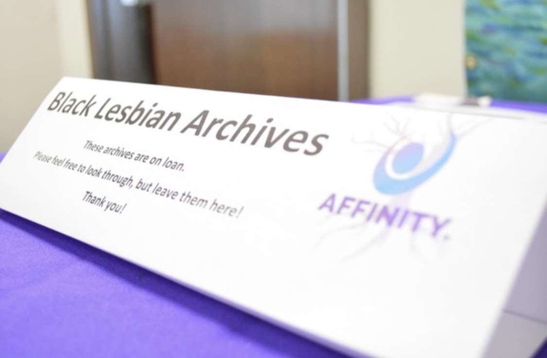 "Table top sign that says ""Black Lesbian Archives. These archives are on loan. Please feel free to look through, but leave them here! Thank you! With Affinity and logo on the right."