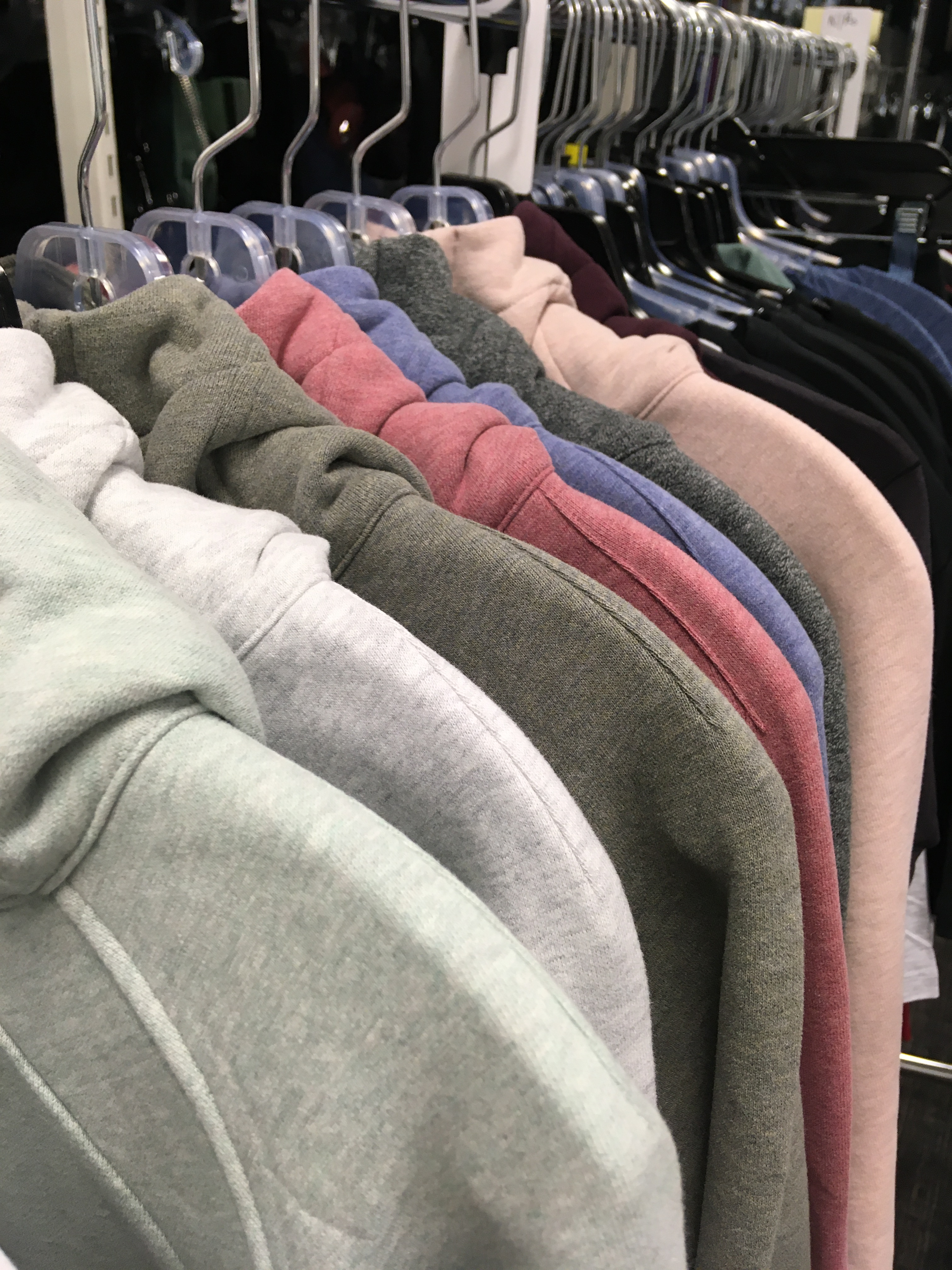 View o f hoodies in pastel and gray shades hanging on a rack.