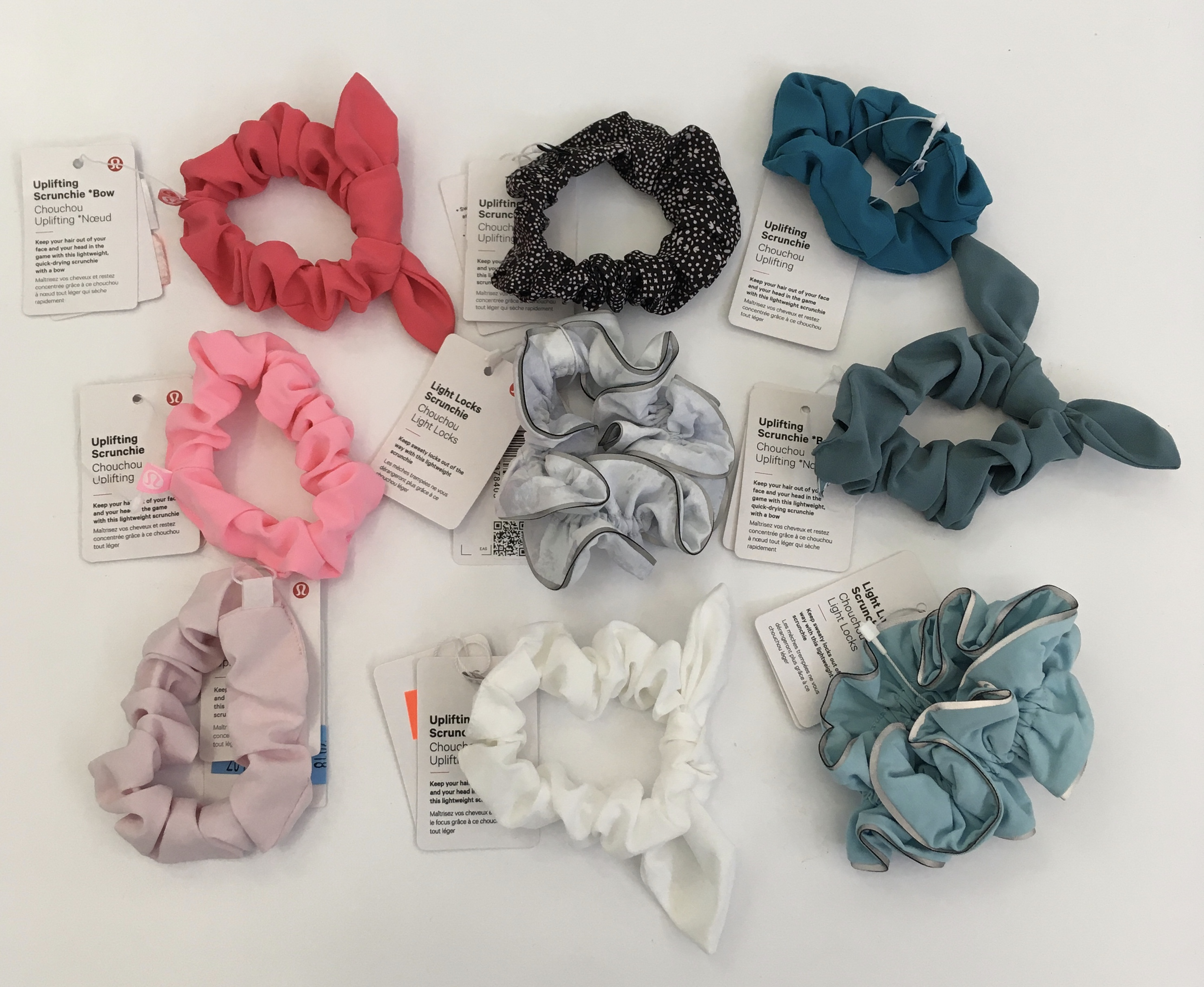 9 scrunchies on display, various colors, w/ exhibit tags.
