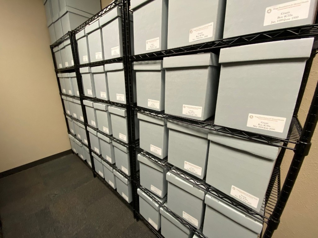 This picture shows a close up of one row where the blue archival boxes and labels can be seen more clearly.